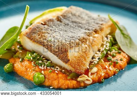 Gourmet dish - salmon with crispy skin with carrots mash. Grilled salmon fillet on carrot espuma. Keto food - baked trout with skin on white background and hard shadow. Menu seafood restaurant