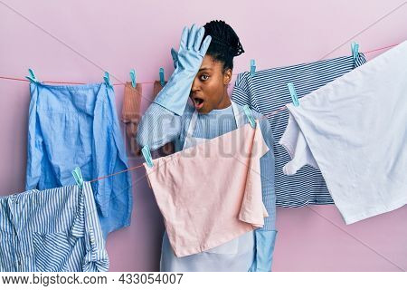 African american woman with braided hair washing clothes at clothesline surprised with hand on head for mistake, remember error. forgot, bad memory concept.