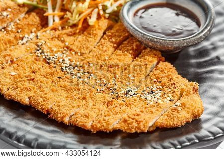 Authentic German schnitzel with cabbage salat and sauce on black plate. Breaded meat - popular restaurant dish Viennese schnitzel. Thin slice of meat breaded with vegetables salad on white background