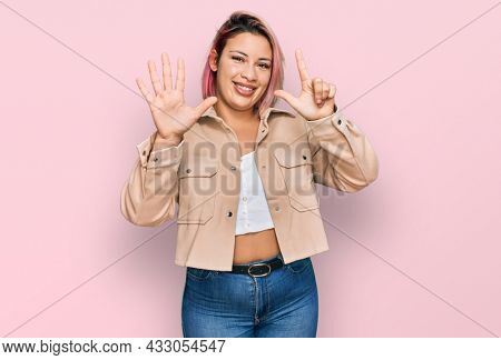 Hispanic woman with pink hair wearing casual clothes showing and pointing up with fingers number seven while smiling confident and happy.