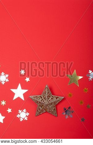 Composition of christmas decorations with stars, snowflakes and copy space on red background. christmas, tradition and celebration concept.