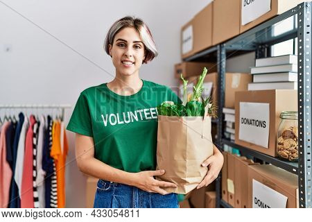Young caucasian volunteer girl holding groceries paper bag working at charity center.