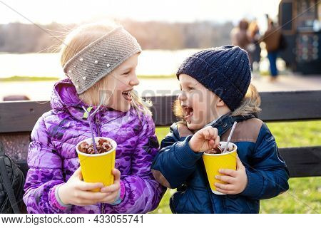 Two Cute Adorable Siblings Children Sitting On Bench Drink Delicious Yummy Hot Chocolate, Tea Cocoa