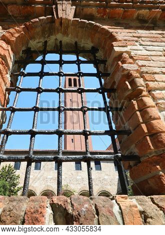 Bell Tower Of The Island Of Santa Elena Seen Through A Metal Grate Near Venice In Italy