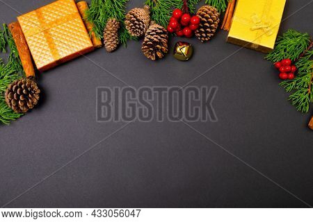 Composition of christmas decorations with presents, pine cones and copy space on black background. christmas, tradition and celebration concept.
