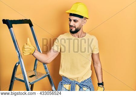Handsome man with beard by construction stairs wearing hardhat looking proud, smiling doing thumbs up gesture to the side