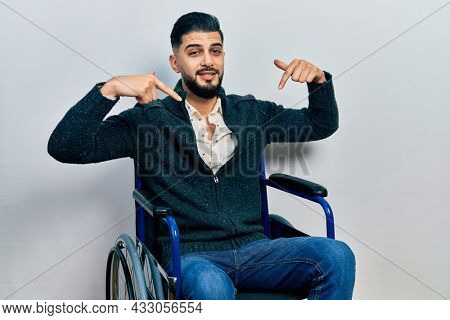 Handsome man with beard sitting on wheelchair looking confident with smile on face, pointing oneself with fingers proud and happy.