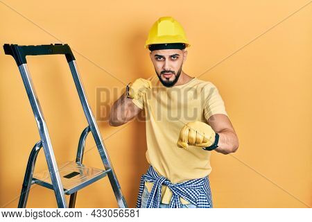 Handsome man with beard by construction stairs wearing hardhat punching fist to fight, aggressive and angry attack, threat and violence