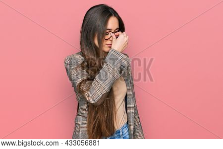 Young hispanic girl wearing business clothes and glasses tired rubbing nose and eyes feeling fatigue and headache. stress and frustration concept.