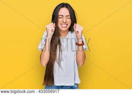 Young hispanic girl wearing casual white t shirt excited for success with arms raised and eyes closed celebrating victory smiling. winner concept.