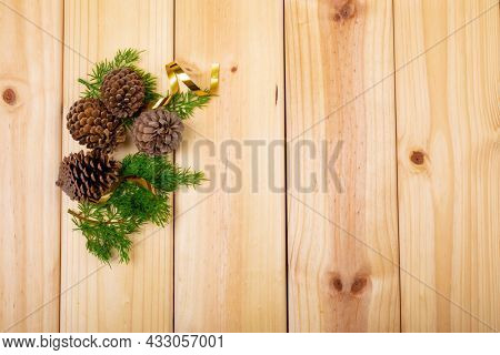 Composition of christmas decorations with pine cones and copy space on wooden background. christmas, tradition and celebration concept.