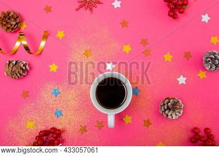 Composition of christmas decorations with pine cones, stars and coffee on pink background. christmas, tradition and celebration concept.