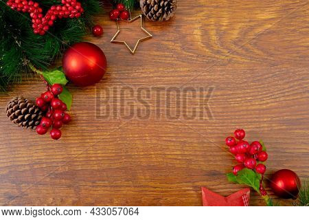 Composition of christmas decorations with pine cones, baubles and copy space on wooden background. christmas, tradition and celebration concept.