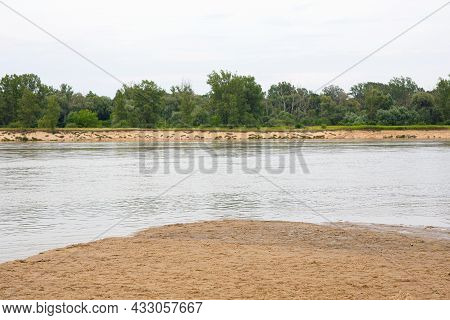 A Calm River, Beach And Green Trees On A Cloudy But Beautiful Day