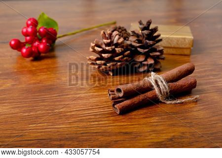 Composition of christmas decorations with pine cones and cinnamon on wooden background. christmas, tradition and celebration concept.