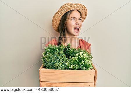 Beautiful brunette little girl wearing gardener hat holding wooden plant pot angry and mad screaming frustrated and furious, shouting with anger. rage and aggressive concept.
