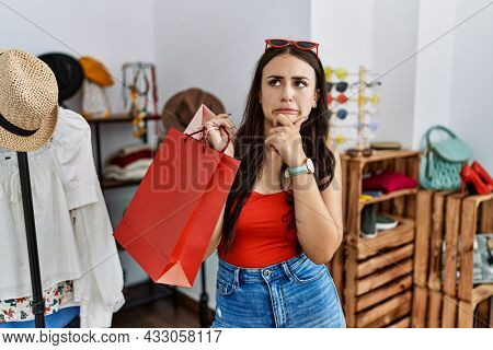 Young brunette woman holding shopping bags at retail shop thinking worried about a question, concerned and nervous with hand on chin