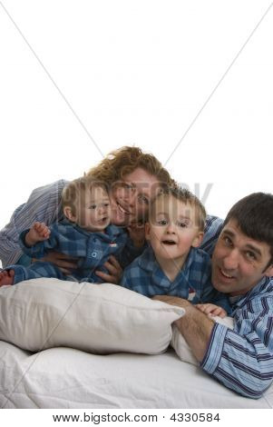 Family Of Four Relaxes In Bed