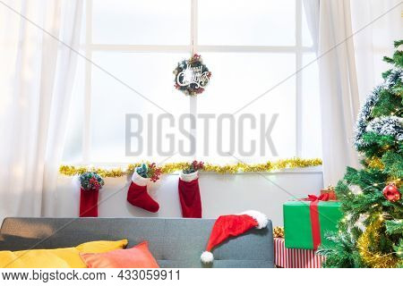 Composition of merry christmas sign in window, with christmas stockings and christmas tree. christmas, tradition and celebration concept.