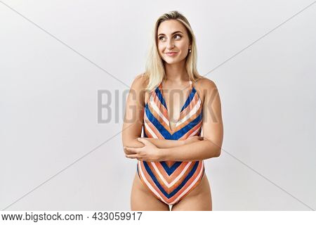 Young blonde woman wearing swimsuit over isolated background smiling looking to the side and staring away thinking.