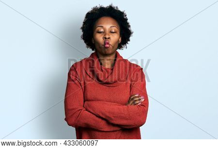 African american woman with afro hair with arms crossed gesture making fish face with mouth and squinting eyes, crazy and comical.