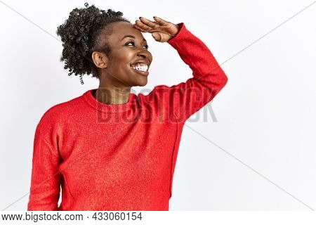 Young african american woman wearing casual clothes over isolated background very happy and smiling looking far away with hand over head. searching concept.