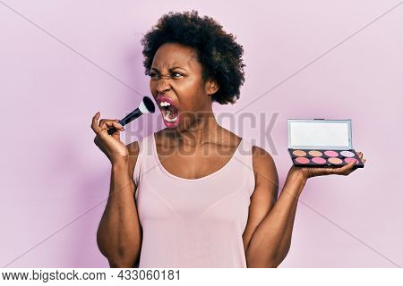 Young african american woman holding makeup brush and blush angry and mad screaming frustrated and furious, shouting with anger. rage and aggressive concept.
