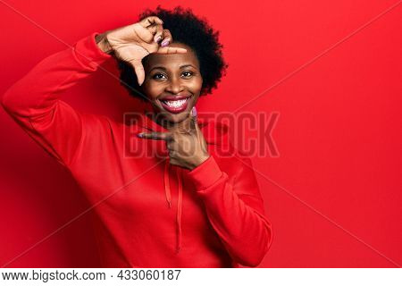 Young african american woman wearing casual sweatshirt smiling making frame with hands and fingers with happy face. creativity and photography concept.