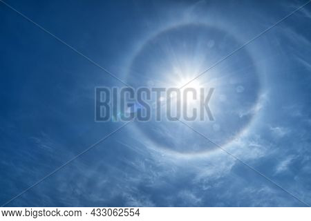 A Halo Around A Radiant Sun With Lens Flare In A Blue Sky.