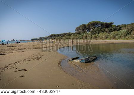 Woman And Her Reflection In The River Flowing Into The Sea At Torre Astura In Italy