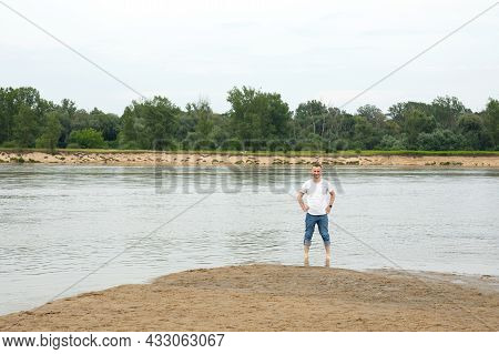 The Image Lonely Positive And Smiling Man On A Beach By The River, Holding His Legs In The Water