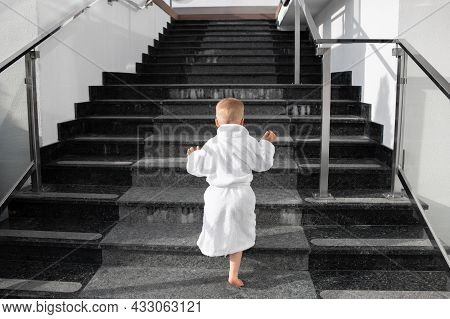 Back View Of Cute Funny Caucasian Blond Kid Boy Wearing White Pool Spa Bathrobe Walking Upstairs On