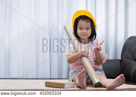Cute Asian Girl Wearing A Yellow Toy Hat Like An Engineer, She Holds A Roll Of Brown Paper Tube, A B