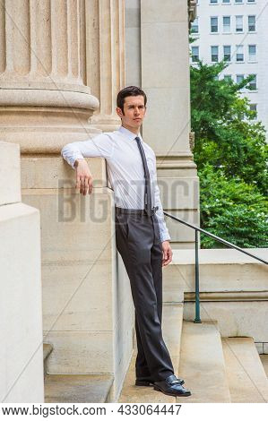 Dressing In A Long Sleeve White Shirt, Black Pants, Leather Shoes, A Black Tie, A Young Layer Is Sta