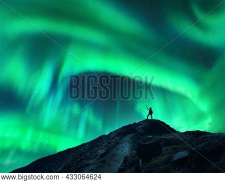 Northern Lights And Silhouette Of Woman With Raised Up Arms