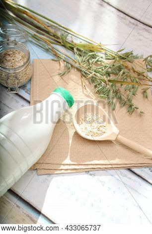 Oat Spikelets, A Wooden Spoon With Oat Flakes And A Bottle Of Oat Milk On The Table With Sun Glare.