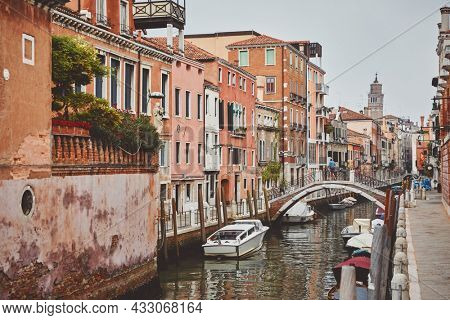 Channel in Venice with bridge boat gondola and old authentic italian houses. Cloudy day in old town. Italy.