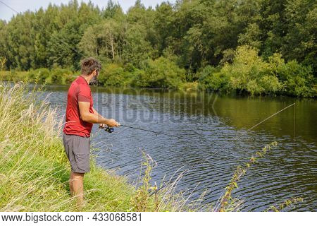 A Man With A Beard Is Fishing On The River. A Fisherman With A Fishing Rod Is Fishing On The River B