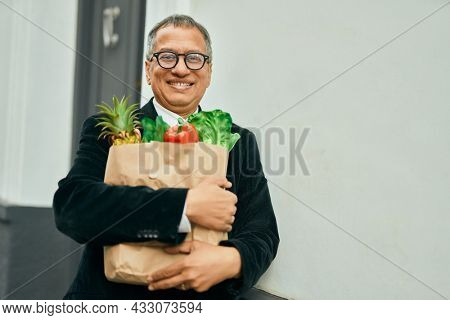Middle age southeast asian man smiling holding a bag of fresh groceries standing by home door