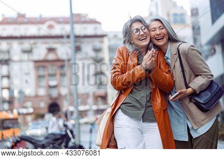 Joyful Senior Woman And Asian Companion Holding Smartphone Stand On Modern City Street