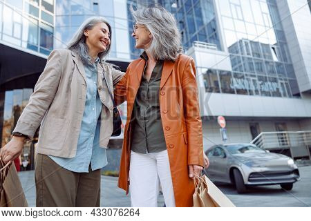 Smiling Grey Haired Asian Woman Hugs Mature Lady Holding Shopping Bags On City Street