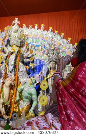 Howrah, West Bengal, India - 24th October 2020 : Masked Hindu Devotee Woman Is Playing Conch While G