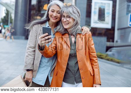 Smiling Silver Haired Lady And Companion With Shopping Bags Take Selfie On Modern City Street