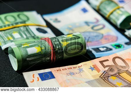 Close Up Of Euro Money Roll. Euro Banknote Set Cash Money - Eu Currency. Rolled With Rubber Euro Not