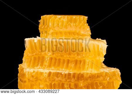 Close Up Stack Of Several Fresh Cut Golden Comb Honey Slices On Plate Isolated On Black Background,
