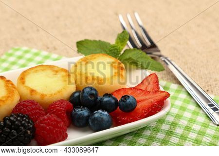 Close Up Serving Portion Of European Quark Cheese Pancakes Dessert With Fruits On Table, High Angle