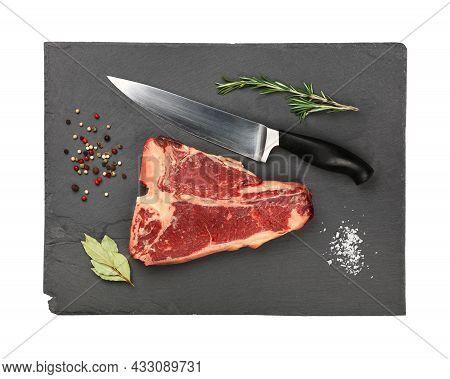 Close Up One Marbled Raw Porterhouse T-bone Beef Steak With Rib Bone On Black Slate Cutting Board Wi