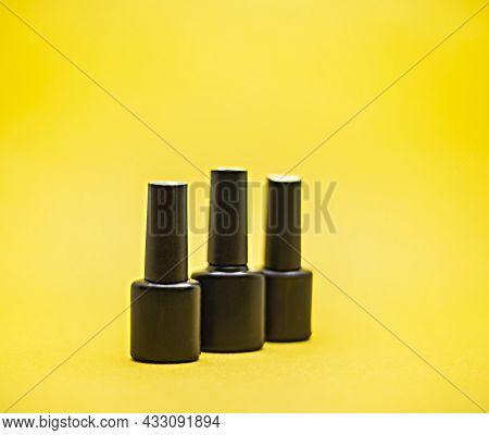 Three Black Bottles Of Gel Nail Polish On A Yellow Background, Image For Advertising Nail Polish
