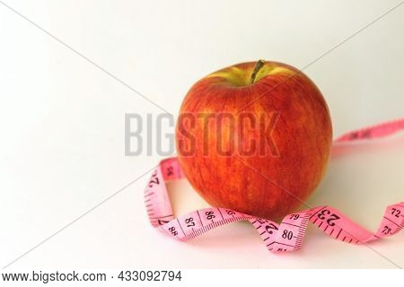 Red Apple And Tape Measure Close Up.