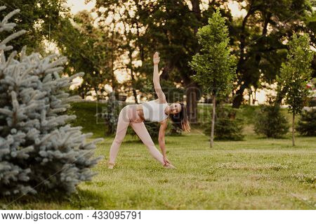Peaceful, Fit Woman Stand In Triangle Pose And Do Yoga At Sunset In Park In Summer, Concept Of Medit